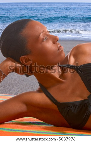 African-American female relaxing and taking sunbath by sea