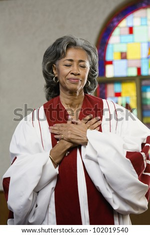 African American female Reverend with hands on heart - stock photo