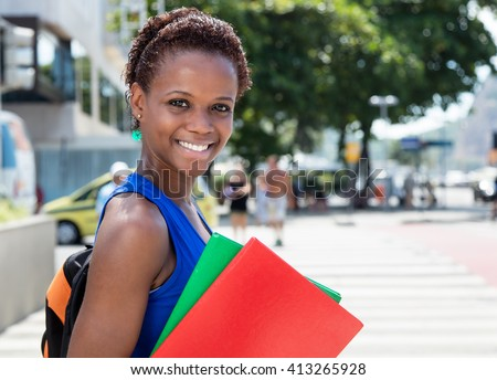 African american female student with short hair in city