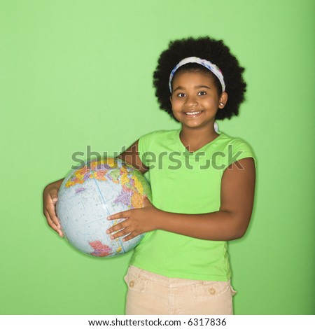 African American girl holding globe at hip and smiling at viewer.