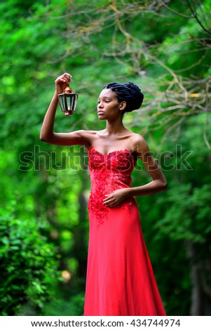 African American girl in a red dress, with dreadlocks, with a lamp and a candle in his hand, stands in the Park in the summer on a background of green plants and looks at the fire. Vertical view - stock photo