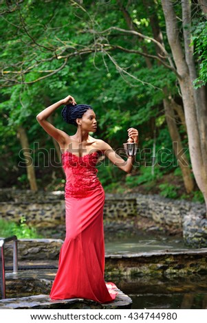 African American girl in a red dress, with dreadlocks, with a lamp and a candle in his hand, stands in the summer in the Park near the water on a background of green plants and looking to the side. - stock photo