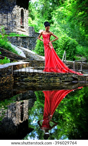 African American girl in a red dress with red shoes in hand is worth in the summer on the water on the stones in the Park on a background of green plants and is reflected in the water. Vertical view - stock photo