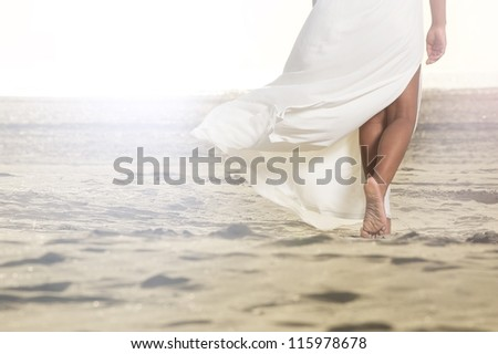 African American girl is walking on the sand with a flowing white dress. - stock photo
