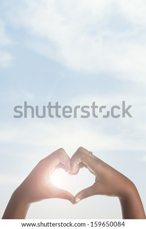 African american girl making heart shape with hands around sun.  - stock photo