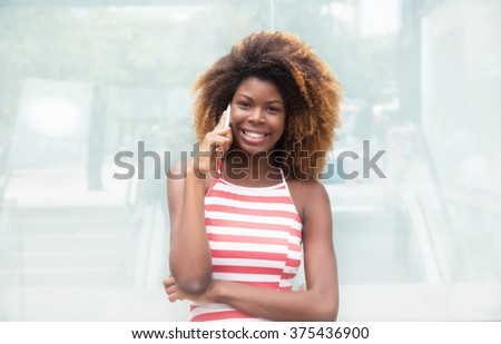 African american girl with crazy hairstyle talking at phone - stock photo