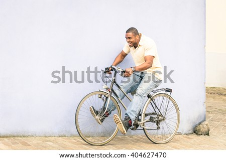 African american guy having fun with vintage bicycle - Free time with young man riding bike in urban city area - Freedom and carefree concept with afroamerican person enjoying everyday life moments - stock photo