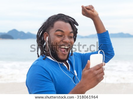 African american guy with dreadlocks listening to music at beach - stock photo
