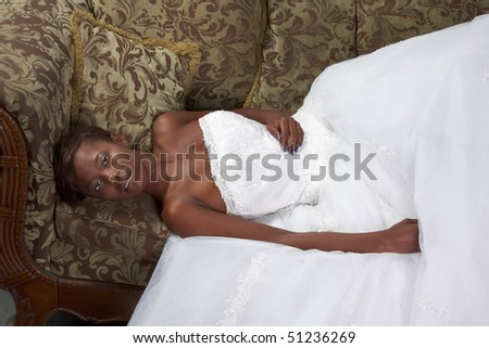 African American happy female in white gorgeous wedding gown lying down on couch