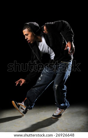 African American hip hop dancer performing over a dark background - stock photo