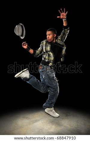 African American hip hop dancer performing with hat over dark background with spotlight - stock photo