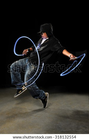African American hip hop dancer with LED lights over dark background - stock photo