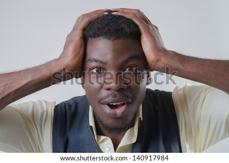 African-American holds his hands behind his head