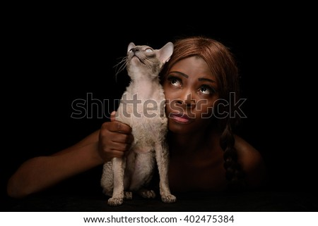 African-american lady and her cat looking up together. Black background