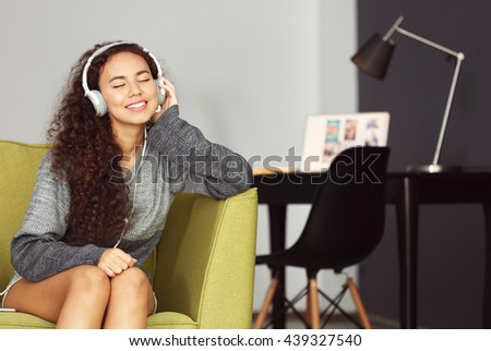African American listening to music in headphones in green armchair - stock photo