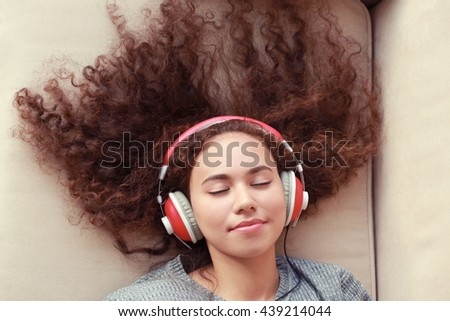 African American listening to music in headphones on the couch - stock photo