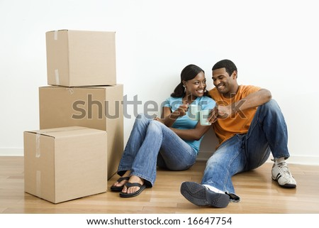 African American male and female couple sitting on floor next to moving boxes relaxing. - stock photo