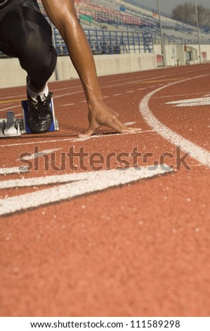 African American male athlete at starting line in racetrack - stock photo