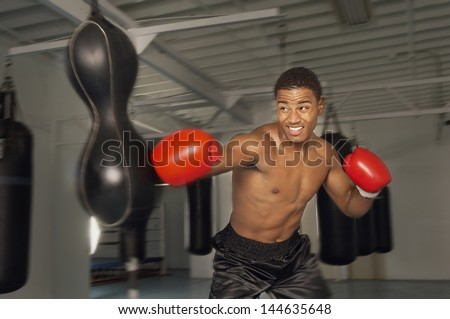 African American male boxer hitting punch bag in red gloves in the gym - stock photo