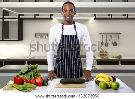 African American male chef wearing an apron in a home or restaurant kitchen.  He is trying to prepare a healthy vegan or vegetarian meal. - stock photo