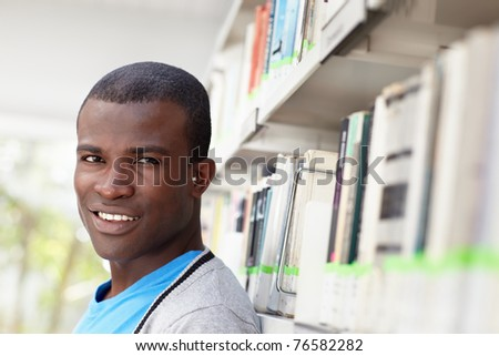african american male college student leaning on shelf in library and looking at camera. Horizontal shape, head and shoulders, copy space