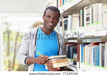 african american male college student leaning on shelf in library and looking at camera. Horizontal shape, waist up, front view - stock photo