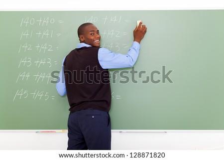 african american male elementary school teacher erasing chalkboard - stock photo