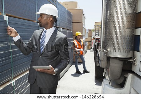 African American male engineer inspecting planks while female worker standing by flatbed truck - stock photo