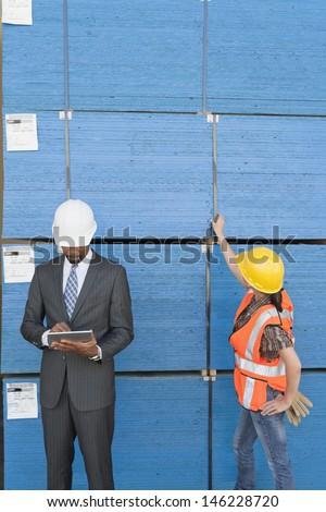 African American male engineer working on tablet PC while female industrial worker checking wooden planks - stock photo