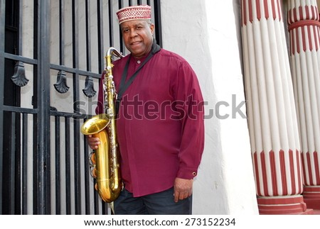 African american male jazz musician with his saxophone outside. - stock photo