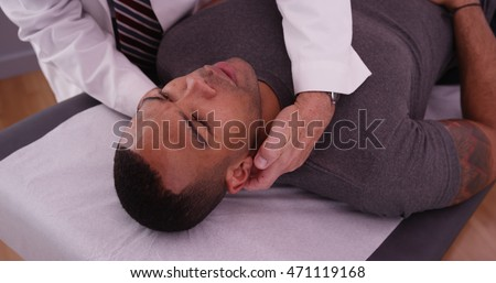 African-american male patient having neck pain examined by chiropractor.