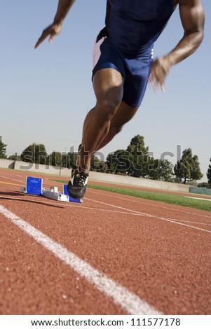 African American male runner beginning race - stock photo