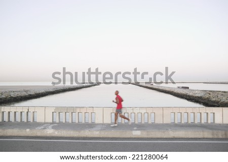 African American male runner on bridge - stock photo