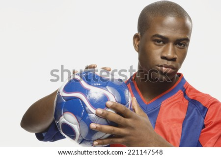 African American male soccer player holding ball - stock photo