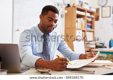 African American male teacher working at his desk - stock photo