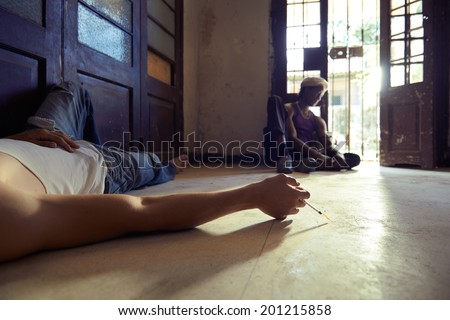 African american man and caucasian guy in overdose, injecting heroine with syringe and lying on floor - stock photo