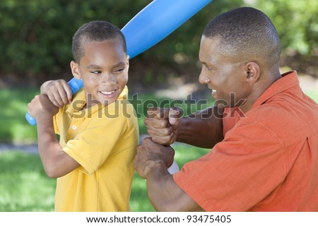 African American man & boy child, father and son playing baseball together outside. - stock photo