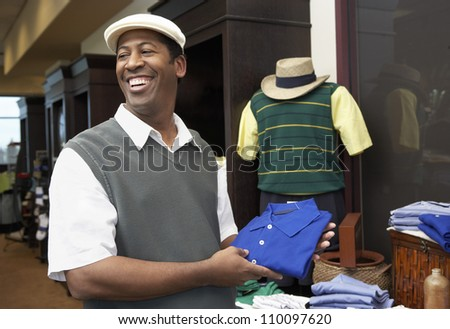 African American man buying clothes in clothing store - stock photo