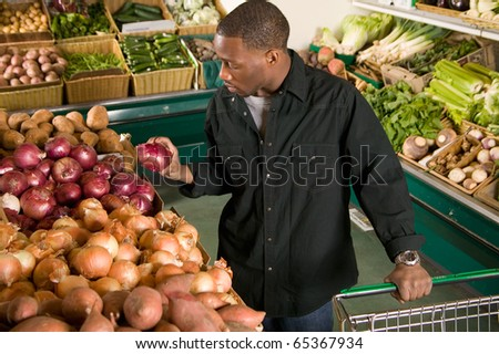 African American man choosing vegetables in supermarket