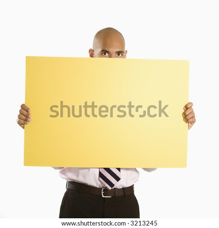 African American man holding and peeking over blank yellow sign. - stock photo
