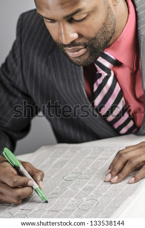 African American Man Hunting For A Job In The Classifieds - stock photo