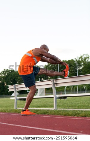 African American man in his 30s stretching at a sports track outdoors. - stock photo