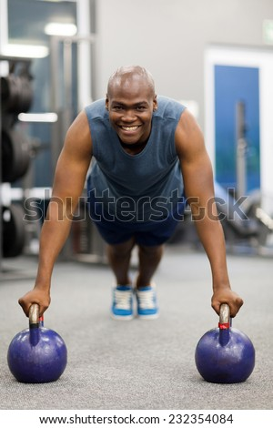 african american man in plank position with kettle bells - stock photo