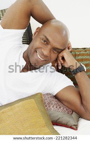 African American man laying on pillows - stock photo