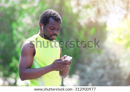 African American man listening music with earphones over green trees background