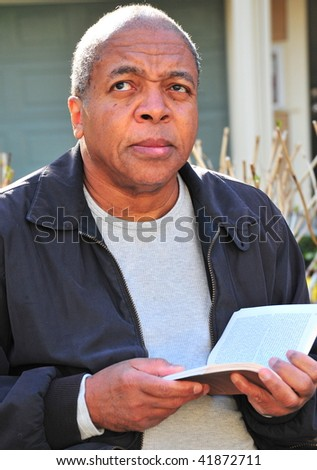 African american man reading a book outside.