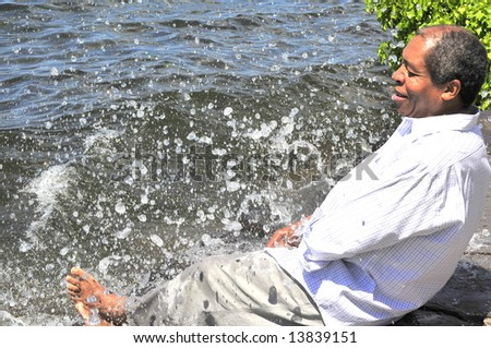 African american man relaxing on the beach. - stock photo