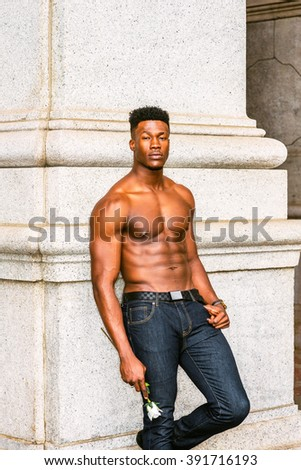 African American Man seeking love in New York. Shirtless, half naked, waring blue jeans, a young, strong, sexy guy standing by column on street, holding white rose, waiting. Instagram filtered effect.