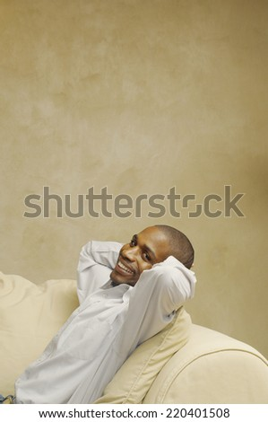 African American man sitting on sofa - stock photo