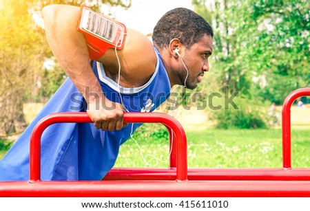 African american man sport exercise listening music with earphones at city park - Black handsome guy workout triceps session outdoors - Concept of strength determination and healthy lifestyle - stock photo